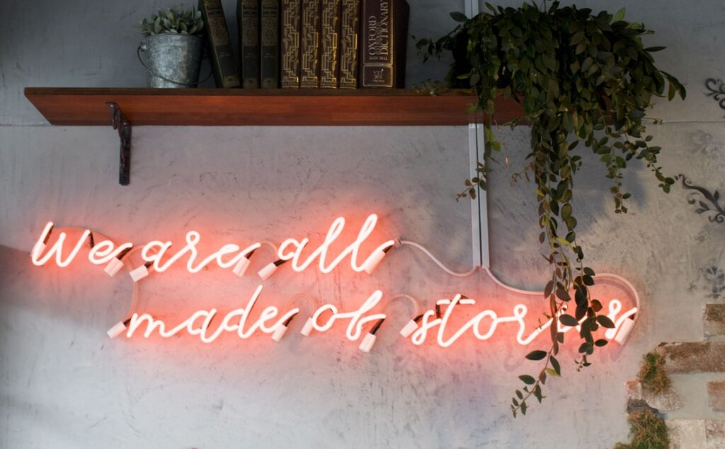 """A wall with neon lights stating, """"we are all made of stories"""""""